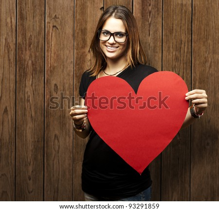 portrait of a pretty woman holding a paper heart against a wooden wall - stock photo