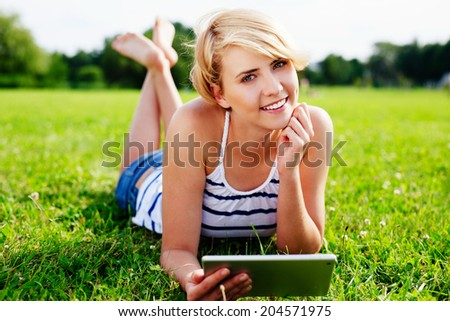 Portrait of a pretty woman lying on the grass with a digital tablet in her hand - stock photo