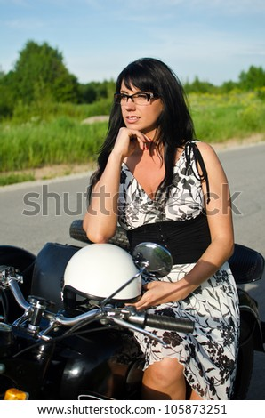 Portrait of a pretty woman on a retro motorcycle - stock photo