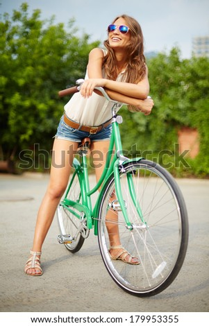 Portrait of a pretty woman on bicycle enjoying summer day in the park - stock photo