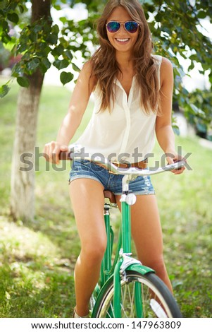 Portrait of a pretty woman on bicycle in the park - stock photo