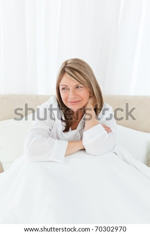 Portrait of a pretty woman on her bed at home - stock photo
