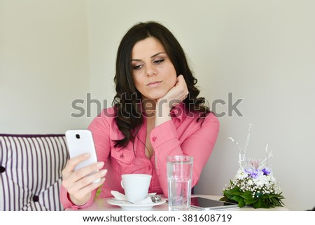 Portrait of a pretty woman reading message on her cell telephone while sitting in cool modern coffee shop interior, young charming caucasian female chatting on mobile phone during morning breakfast - stock photo