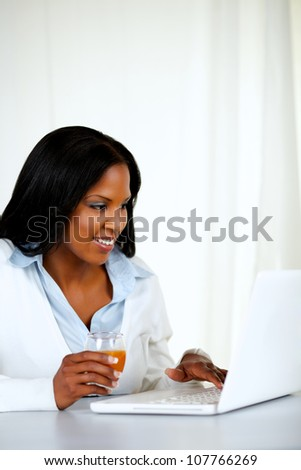 Portrait of a pretty woman smiling and using a laptop while drinking an healthy orange juice at soft composition - stock photo