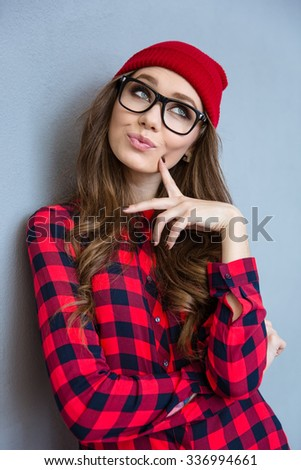 Portrait of a pretty woman thinking over gray background - stock photo