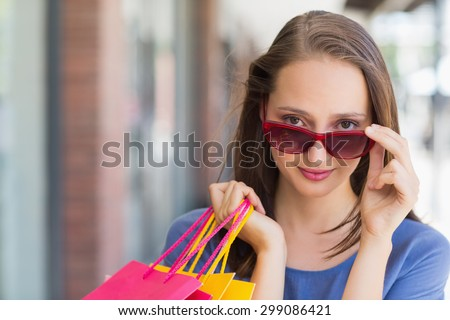 Portrait of a pretty woman tilting her sunglasses