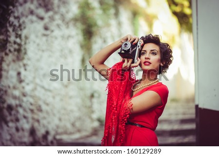 Portrait of a pretty woman, vintage style, in urban background, wearing a red dress taking photographs with a old camera - stock photo