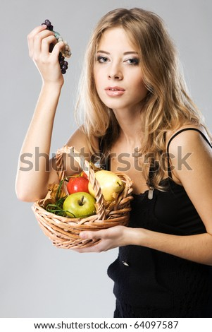 Portrait of a pretty woman with a basket of ripe fruit - stock photo