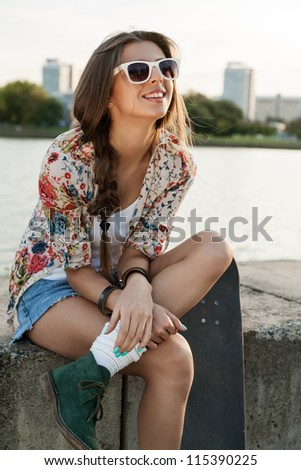 Portrait of a pretty woman with a skateboard, outdoors - stock photo