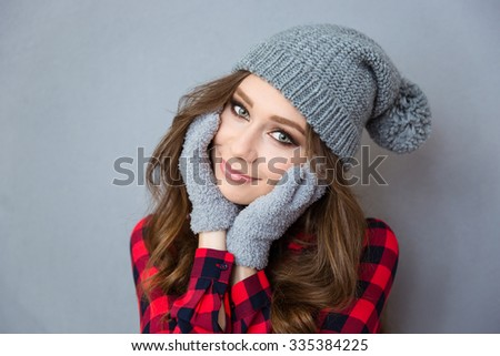 Portrait of a pretty woman with hat and mittens looking at camera over gray background