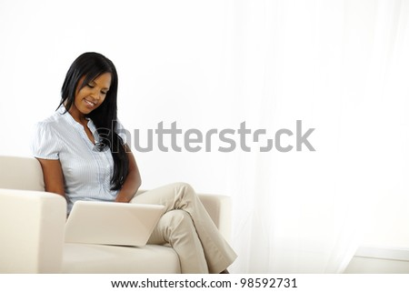 Portrait of a pretty young black woman browsing on laptop while resting at home - stock photo