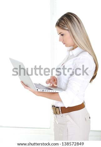 Portrait of a pretty young blonde businesswoman holding a laptop on a white background - stock photo