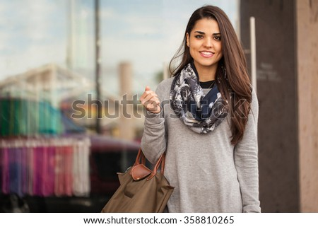 Portrait of a pretty young brunette carrying a purse and standing outside a clothing store in a shopping mall - stock photo