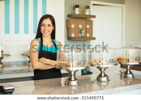 Portrait of a pretty young brunette in an apron selling cookies and pastries in a cake shop - stock photo