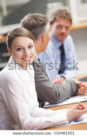 Portrait of a pretty young businesswoman smiling in a meeting  - stock photo
