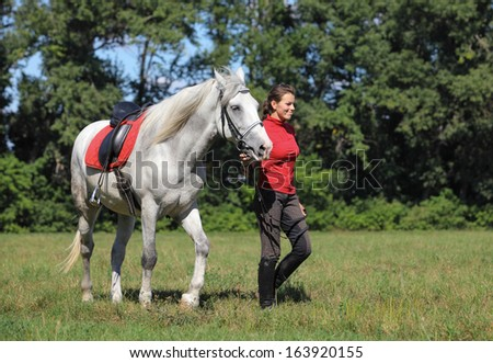 Portrait of a pretty young equestrian girl with horse - stock photo