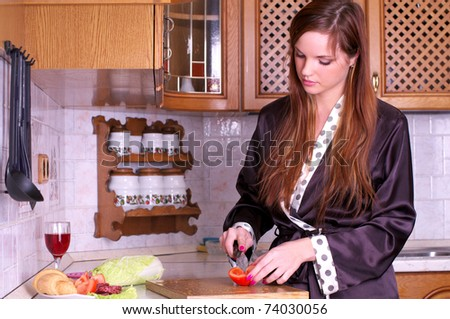 Portrait of a pretty young female preparing healthy food at domestic kitchen - stock photo