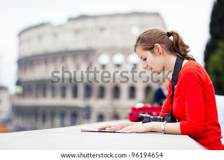 Portrait of a pretty, young, female tourist in Rome, Italy (with Colloseum in the background) - stock photo
