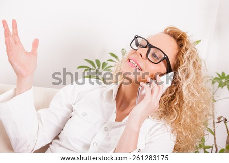 Portrait of a pretty young girl having phone conversation at home - stock photo