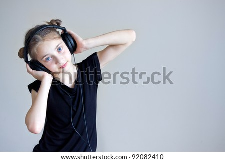 Portrait of a pretty young girl in headphones listen to music on gray background