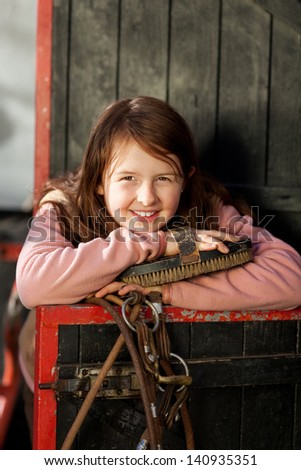 Portrait of a pretty young girl posing behind a stable door with the horse head piece and a large brush - stock photo