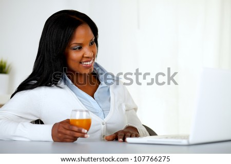Portrait of a pretty young girl relaxing on laptop at soft colors composition - stock photo