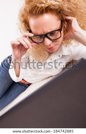 Portrait of a pretty young girl working on her laptop at home