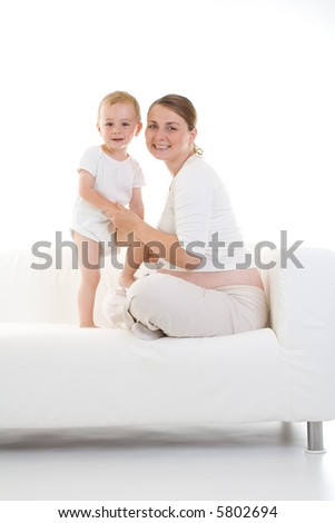 Portrait of a pretty young mother sitting on a white couch with her young child...isolated view, facing the camera. - stock photo