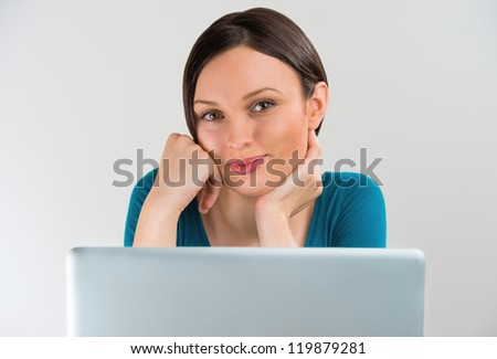 Portrait of a pretty young student girl smiling with a laptop - stock photo