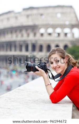 Portrait of a pretty young tourist taking photographs while sightseeing in Rome, Italy (with Colosseum in the background) - stock photo