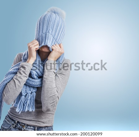 portrait of a pretty young woman covering her head with a wool cap - stock photo