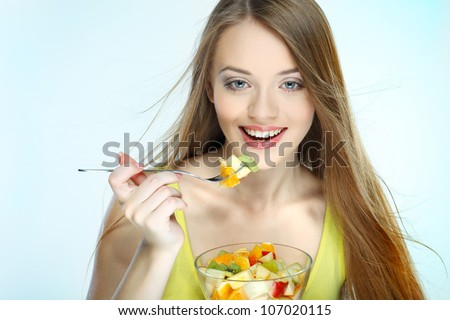 Portrait of a pretty young woman eating fruit salad - stock photo