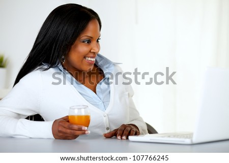 Portrait of a pretty young woman having fun on laptop screen at home indoor - stock photo