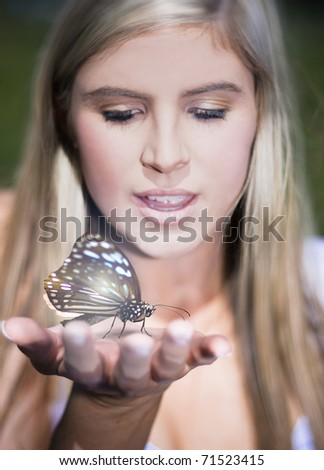 Portrait Of A Pretty Young Woman Holding A Large Butterfly In Her Outstretched Hand - stock photo