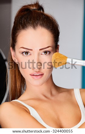 Portrait of a pretty young woman holding powder brush - stock photo