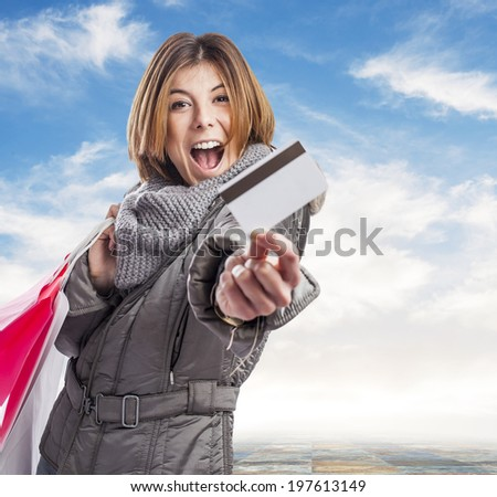 portrait of a pretty young woman holding shopping bags and showing her credit card - stock photo