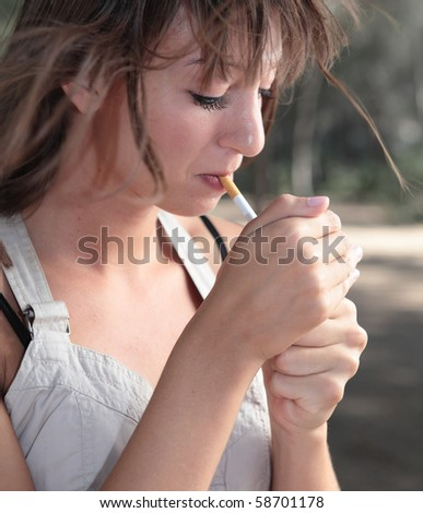Portrait of a pretty young woman lighting a cigarette outdoors - stock photo