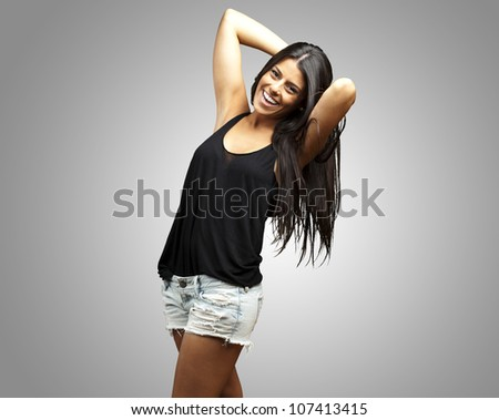 portrait of a pretty young woman posing over a grey background