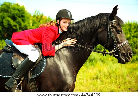 portrait of a pretty young woman riding a black horse - stock photo