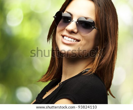 portrait of a pretty young woman smiling against a green background