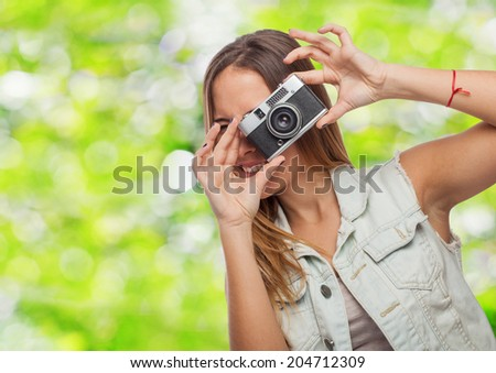 portrait of a pretty young woman taking photo with her camera