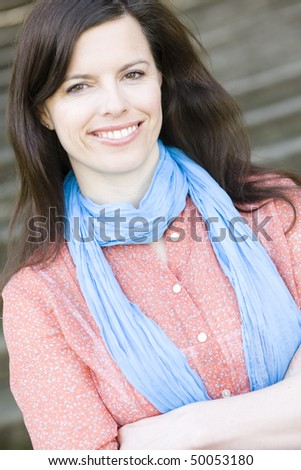 Portrait of a Pretty Young Woman Wearing a Blue Scarf Smiling To Camera - stock photo