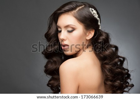 Portrait of a pretty young woman with a beautiful bridal hairstyle and makeup. Brunette with long wavy hair - stock photo