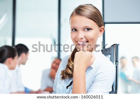 Portrait of a pretty young woman with her team in the background  - stock photo