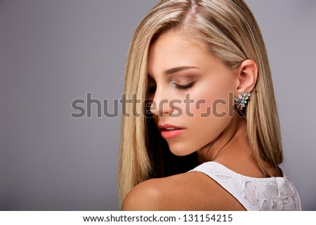Portrait of a pretty young woman with long blond hair and closed eyes on gray background - stock photo