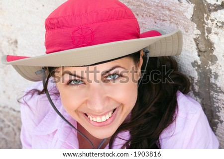 Portrait of a pretty young woman with pink hat looking up