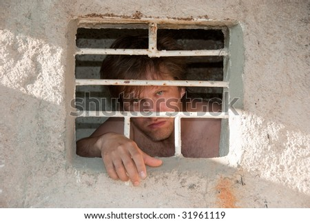 Portrait of a prisoner behind a grate - stock photo