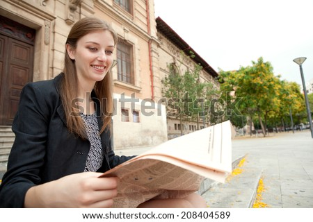 Portrait of a professional business woman sitting at the entrance of an official office building reading a financial newspaper and smiling, outdoors. Corporate business in the financial city. - stock photo