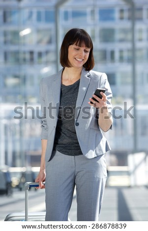 Portrait of a professional business woman traveling. Woman reading text message on mobile phone - stock photo