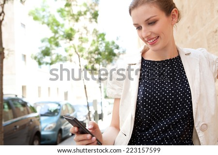 Portrait of a professional business woman using a smartphone technology device to access the internet while working and leaning on a stone wall, smiling in the city. Business lifestyle technology.